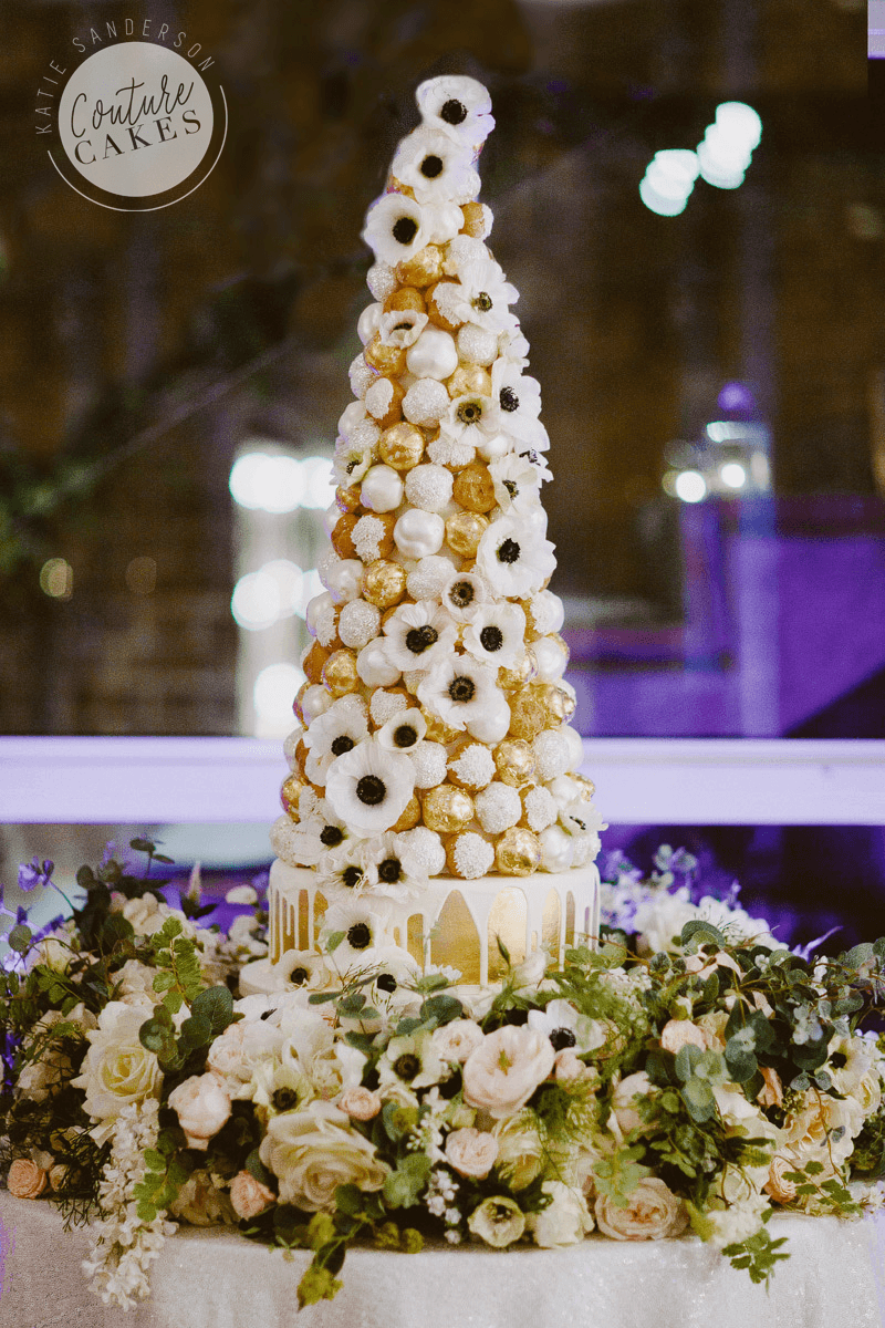 Croquembouche with serves 200 profiteroles £445, plus cake serves 75 portions £195, optional gold leaf £50 gold. Flowers provided by brides florist.